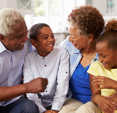 children sitting with their grandparents smiling and laughing