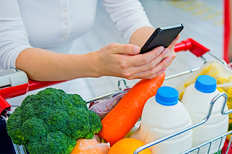 Woman with phone in her hand with vegetables and milk in her cart