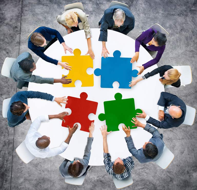 people sitting around a table with 4 large puzzle pieces